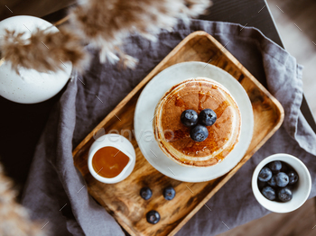 Top view of American traditional pancakes with honey and fresh blueberry