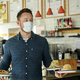 Waiter wearing mask holding two plates of food for customers