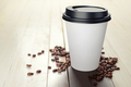 330 ml disposable coffee paper cup with beans on white wooden table. - PhotoDune Item for Sale