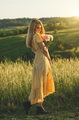 Young blond caucasian female model with flowers in her hand stands at green meadow summer sunny day. - PhotoDune Item for Sale