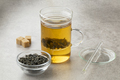 Tea glass with green gunpowder tea and a bowl with dried tea leaves - PhotoDune Item for Sale