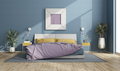 Colorful double bed in a modern room with blue walls - PhotoDune Item for Sale