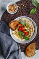 Hummus with green pea, pine nuts, tomatoes and swiss chard. Vegetarian healthy dish, top view. - PhotoDune Item for Sale