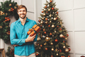 Portrait of young handsome man with gift box posing near Christmas tree - PhotoDune Item for Sale