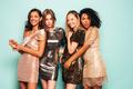 Portrait of four young beautiful women in dresses posing in studio - PhotoDune Item for Sale