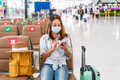 Young woman wearing a surgical mask waiting for a flight at the airport - PhotoDune Item for Sale