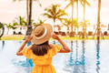 Young woman traveler enjoying the sunset by a tropical resort pool while traveling - PhotoDune Item for Sale