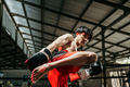 Muscular male fighter in boxing gloves makes knee kick on the boxing ring - PhotoDune Item for Sale
