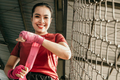 smiling muscled asian woman fighter wearing red strap on wrist - PhotoDune Item for Sale