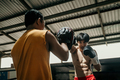 young man boxer doing exercise hitting punching competing with his trainer - PhotoDune Item for Sale