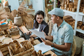 a craftsman shows a letter of agreement to a businesswoman - PhotoDune Item for Sale