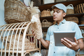 young entrepreneur checks a woven bag while holding a pad - PhotoDune Item for Sale