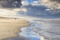 couple walking on sunny stormy beach - PhotoDune Item for Sale