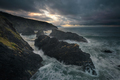 Stormy seascape sunset scene with black rocks - PhotoDune Item for Sale