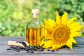 Bottle of sunflower oil and sunflower flowers with seeds on wooden table - PhotoDune Item for Sale