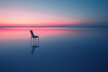 Chair among smooth water of lake at the sunset - PhotoDune Item for Sale