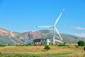 Wind turbine and house on hill under blue sky - PhotoDune Item for Sale