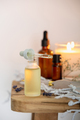 White scented candle, body lotion, essential oils and delicate flowers on wooden bench - PhotoDune Item for Sale