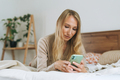 Beautiful blonde young woman using mobile on bed - PhotoDune Item for Sale