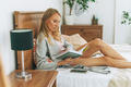 Friendly charming blonde woman reading book on bed in bright interior - PhotoDune Item for Sale