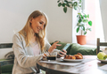Beautiful blonde young woman having breakfast and using mobile in living room at the home - PhotoDune Item for Sale