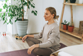 Beautiful blonde young woman in comfortable sport wear practice yoga in cozy bedroom at the home - PhotoDune Item for Sale