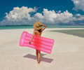 Woman with pink inflatable raft at the beach - PhotoDune Item for Sale