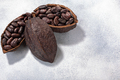 Split fermented cocoa pod with shelled cacao beans atop light grey backdrop, top view,  copy space - PhotoDune Item for Sale