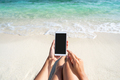 Young woman using mobile phone at beautiful tropical white sand beach - PhotoDune Item for Sale