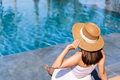 Young woman traveler relaxing and enjoying by a tropical resort pool - PhotoDune Item for Sale