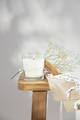 White burning candle and delicate flowers on wooden bench - PhotoDune Item for Sale