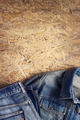 Denim jeans on chipboard wooden background texture - PhotoDune Item for Sale