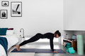 Side view of young slim woman practicing yoga in Plank position in modern bedroom - PhotoDune Item for Sale