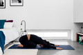 Young slim woman practicing yoga in extended child position in modern minimalistic bedroom - PhotoDune Item for Sale