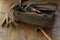 Antique tools and grungy toolbox on rough dark wood surface - PhotoDune Item for Sale