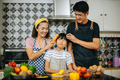 Cute girl help her parents are cutting vegetables smiling while cooking together in kitchen at home. - PhotoDune Item for Sale