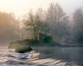 The water gilded from the dawn light flows over little dams of a stone mill - PhotoDune Item for Sale