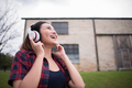 Young woman listening to music with mobile phone outdoor. Happy listening to music with earphone. - PhotoDune Item for Sale