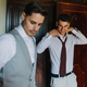 Groom and best man putting on the suit