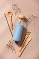 Zero waste, eco friendly concept. Reusable glass bottle and bamboo cutlery. - PhotoDune Item for Sale