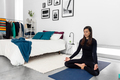Young woman practicing yoga and meditation in lotus pose in bedroom - PhotoDune Item for Sale