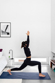 Fit woman practicing Warrior I pose during a yoga training session at home - PhotoDune Item for Sale