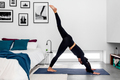 Woman doing one leg downward facing dog split during a yoga practice at modern minimalistic bedroom - PhotoDune Item for Sale