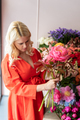 Beautiful blonde florist woman picks up flowers and creates wonderful bouquet - PhotoDune Item for Sale