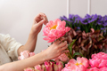 Hands of a young florist woman making modern bouquet of flowers - PhotoDune Item for Sale