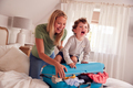 Mother And Son Packing For Vacation With Boy Standing On Full Suitcase To Close - PhotoDune Item for Sale