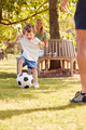 Family With Young Son Having Fun In Park Playing Football And Sitting On Seat Under Tree - PhotoDune Item for Sale