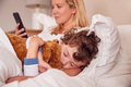Young Son Cuddles Teddy Bear In Parents Bed Whilst Mother Looks At Mobile Phone - PhotoDune Item for Sale