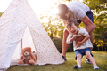 Father And Son Having Fun With Tent Or Tepee Pitched In Garden - PhotoDune Item for Sale