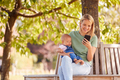 Mother Sitting On Park Bench Under Tree With Baby Daughter Looking At Mobile Phone - PhotoDune Item for Sale